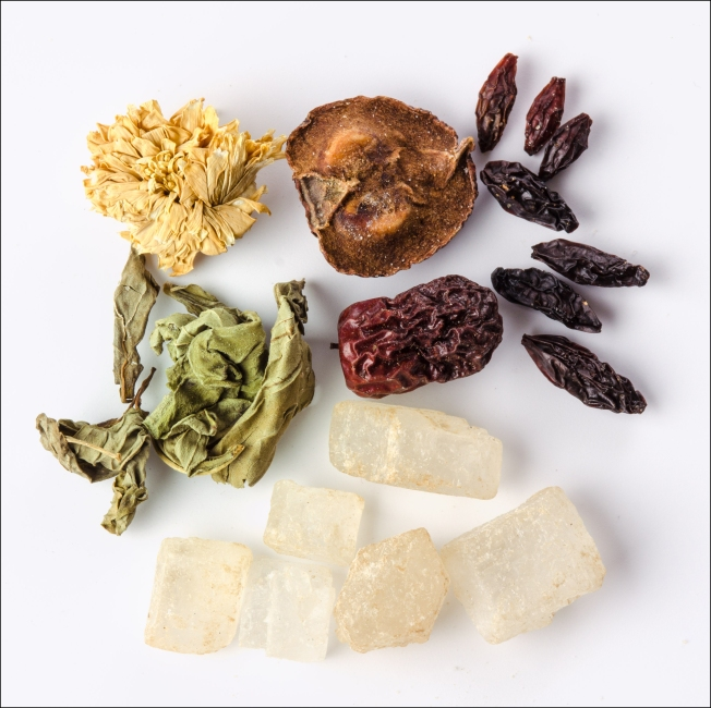 Chrysanthemum tea blend. The Chrysanthemum flower is  on the top left, clockwise two fruits, seven goji berries, rock sugar on the bottom and green tea leaves on the left